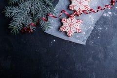 羊皮纸片断用在一个云杉的分支旁边的一个饼干在石背景 库存图片