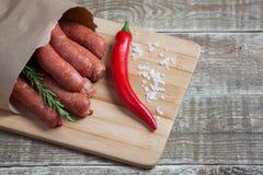 羊羔未加工的自创香肠用迷迭香和辣椒在纸信封,在一个竹切板 库存照片
