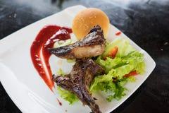 羊羔肉烤牛排在切片切开了用圆的面包、沙拉、油、调味汁和杯子橙汁 免版税库存照片