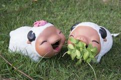 绵羊陶瓷玩偶庭院草两年轻人概念 免版税库存照片