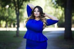 年轻美丽加上在户外蓝色礼服的大小模型,自然的xxl妇女 免版税图库摄影