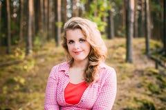 美丽加上摆在夏天森林里的衬衣的大小少妇 免版税库存照片