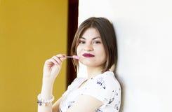 美丽和微笑的女孩拿着一个棒棒糖在yelow和白色背景 免版税库存图片