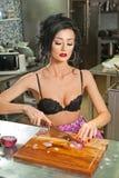 美丽和性感的妇女在厨房里 准备食物的微笑的浅黑肤色的男人 佩带黑胸罩的女孩切有些葱 库存图片