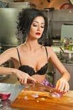 美丽和性感的妇女在厨房里 准备食物的微笑的浅黑肤色的男人 佩带黑胸罩的女孩切有些葱 免版税库存照片