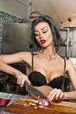 美丽和性感的妇女在厨房里 准备食物的微笑的浅黑肤色的男人 佩带黑胸罩的女孩切有些葱 库存照片