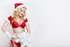 美丽和性感的妇女穿戴作为性感的圣诞老人 免版税图库摄影