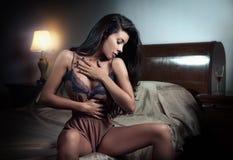 美丽和性感的深色的少妇在床上的穿棕色女用贴身内衣裤。时尚室内射击女用贴身内衣裤。性感的女孩在床上 免版税库存图片