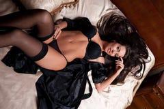 美丽和性感的深色的少妇在床上的穿黑女用贴身内衣裤。时尚室内射击女用贴身内衣裤。黑人林的性感的女孩 库存照片