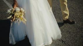 年轻美丽和愉快的走在日落的夫妇新娘和新郎在他们的婚礼的那天 股票录像