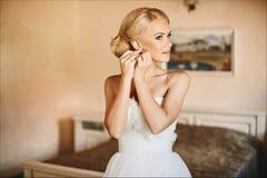 美丽和时兴的年轻新娘、性感的白肤金发的式样女孩有蓝眼睛的和时髦的发型在调整她的ea的白色礼服 免版税库存图片
