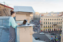 美丽和时髦的女孩为在房子的屋顶的一台膝上型计算机工作在老镇 在桌上也是文件和老加州 免版税库存图片
