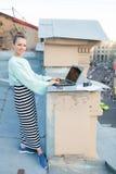 美丽和时髦的女孩为在房子的屋顶的一台膝上型计算机工作在老镇 在桌上也是文件和老加州 库存图片