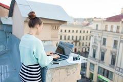 美丽和时髦的女孩为在房子的屋顶的一台膝上型计算机工作在老镇 在桌上也是文件和老加州 免版税库存照片