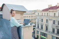 美丽和时髦的女孩为在房子的屋顶的一台膝上型计算机工作在老镇 在桌上也是文件和老加州 图库摄影