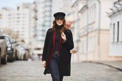 美丽和时髦的女孩,盖帽、外套和太阳镜的,走由街道 免版税库存图片