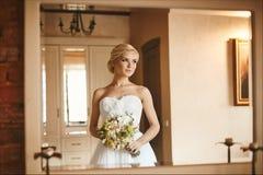 美丽和肉欲的年轻新娘,性感的白肤金发的式样女孩有迷人的微笑的和有花花束的在她的手上 免版税库存照片