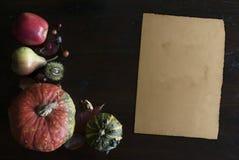 美丽土气完全失败与叶子、南瓜、栗子和老葡萄酒纸板料的位置在木背景 库存图片