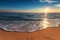 美丽在海运日出 洗涤岸的海浪 库存图片