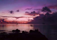 美丽在海运日落 一对夫妇的剪影反对晚上海洋的backround的 紫色色的天空 免版税库存照片