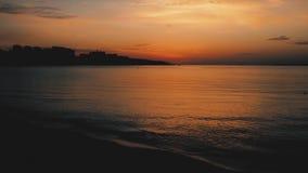 美丽在海运日落 在黑暗的水的红色剧烈的日落 太阳、天空、海、波浪和沙子 股票视频