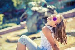 美丽女孩青少年室外 戴括号和眼镜的愉快的青春期前的女孩 夏天热的天 免版税库存图片