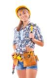 美丽女性建筑工人拿着拔钉锤的和在地平线上方 库存图片