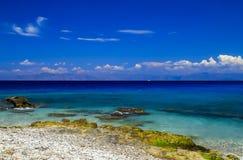 美丽如画的夏天海滩,在海浪的小卵石在美丽的绿松石海,罗得岛排行 图库摄影
