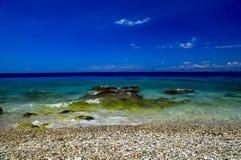 美丽如画的夏天海滩,在海浪的岩石在美丽的绿松石海排行 库存照片