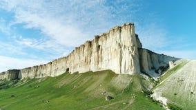 美丽如画的白色峭壁倾斜、石头和小山在美丽的绿色草甸附近反对蓝色多云天空在夏日 影视素材