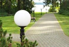 美丽如画的胡同在导致有长凳和美丽的灯笼的一个安静的森林湖的老公园 免版税库存照片
