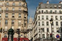 美丽如画的蒙马特街道在与Sacre Couer大教堂的10月下旬在背景中 图库摄影