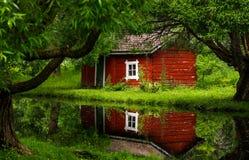 可爱的红色村庄和一个小池塘 免版税库存照片