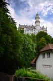 美丽如画的自然风景新天鹅堡城堡,围拢与夏天颜色在巴法力亚阿尔卑斯期间,德国 免版税库存图片