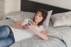 美丽妇女在智能手机写sms在白色T恤杉和蓝色 免版税库存照片