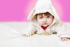 美丽小说谎在她的在一套衣服的腹部的婴儿女孩与耳朵 库存照片