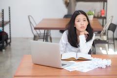美丽工作在网上在膝上型计算机开会和被弄皱的纸的画象亚裔少妇在桌上 库存照片