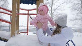 美丽您的有女婴的母亲在降雪的公园 影视素材