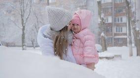 美丽您的有女婴的母亲在降雪的公园 股票视频