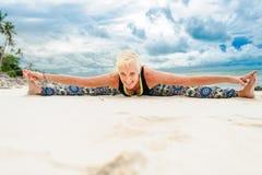 美丽成熟做在沙漠热带beac的年迈的妇女瑜伽 库存照片