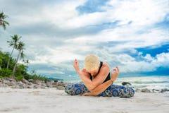 美丽成熟做在沙漠热带beac的年迈的妇女瑜伽 免版税图库摄影