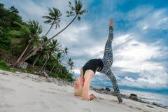 美丽成熟做在沙漠热带beac的年迈的妇女瑜伽 免版税库存图片