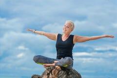 美丽成熟做在沙漠热带beac的年迈的妇女瑜伽 免版税库存照片
