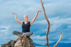 美丽成熟做在沙漠热带beac的年迈的妇女瑜伽 库存图片