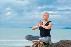 美丽成熟做在沙漠热带beac的年迈的妇女瑜伽 图库摄影