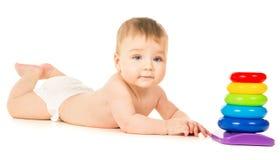 美丽爬行和使用与玩具的一个小婴孩 库存照片