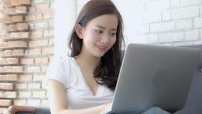 美丽画象亚裔少妇激动和高兴与膝上型计算机的成功在沙发水泥背景 影视素材