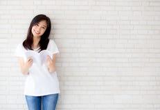 美丽画象年轻亚洲妇女幸福放松在具体水泥白色背景的常设阅读书 免版税库存图片