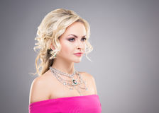 美丽白肤金发在佩带与宝石的一件桃红色礼服一条项链 免版税图库摄影