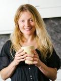 美丽白肤金发在厨房里用咖啡 库存照片